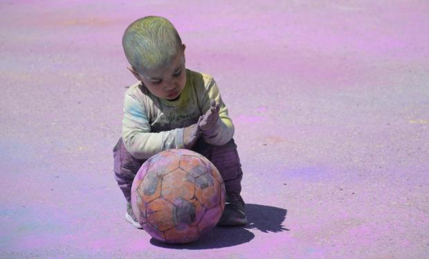 A young boy covered in coloured powder plays with a football during the feast of Holi on March 31 in St Venera. PHOTO: MARK ZAMMIT CORDINA.