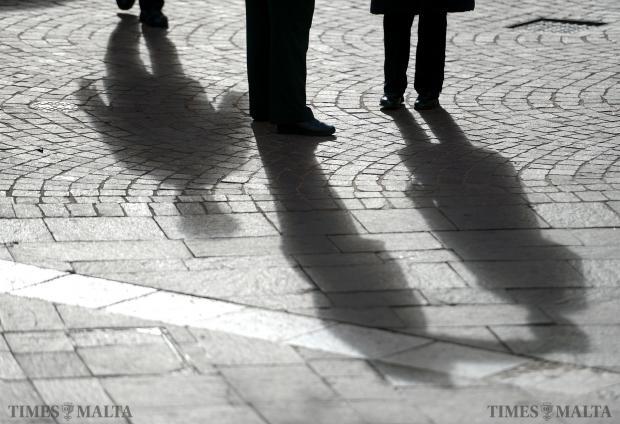The early morning sun breaks through clouds, casting shadows on three pedestrians in Republic Street Valletta on January 5. Photo: Matthew Mirabelli