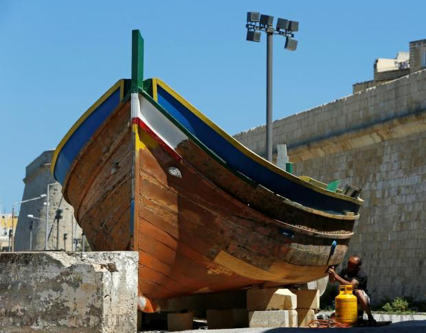 Stripped bare of its traditional bright colours, a luzzu undergoes a throrough makeover at Kalkara Creek on May 16, ahead of its long fishing sprees in the hot months ahead. Photo: Darrin Zammit Lupi