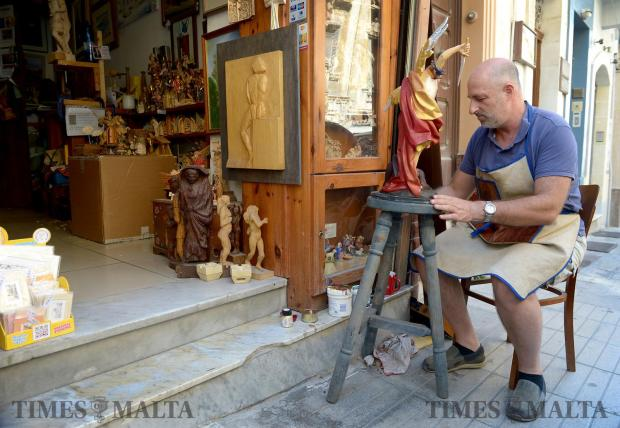 Sculptor Martin Bezzina Wettinger paints a statue of St Michael outside his studio in Old Bakery Street on August 9. Photo: Matthew Mirabelli