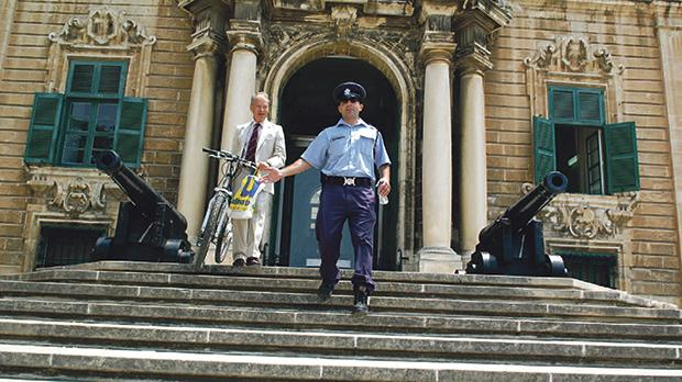 George Debono, who had authored a report on environmental pollution, was led down the steps of Castille by the policeman on duty after he was about to rest his bicycle against one of the cannons outside the Prime Minister's office in June 2008. Photo: Chris Sant Fournier
