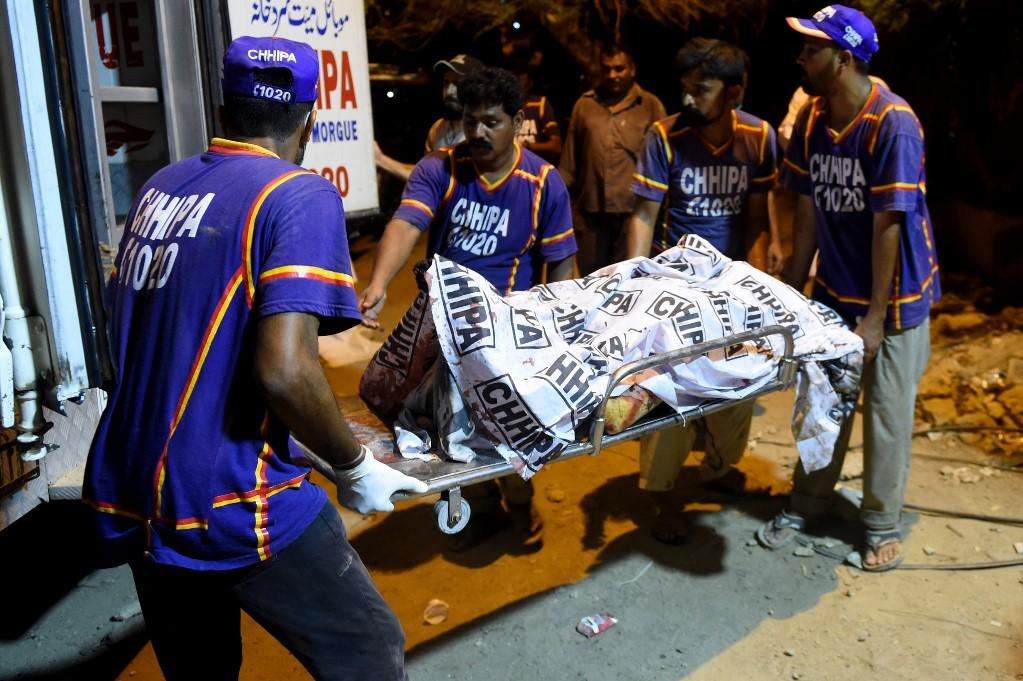Volunteers transport the body of a victim to a hospital. Photo: AFP