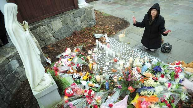 A parishioner paying her respect at a makeshift altar to the victims of an elementary school shooting after attending Sunday Mass at St Rose of Lima Church in Newtown, Connecticut, yesterday. Photo: AFP
