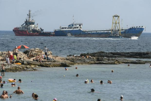 Bathers look on as the tanker is towed away on Wednesday morning. Photo: Jonathan Borg