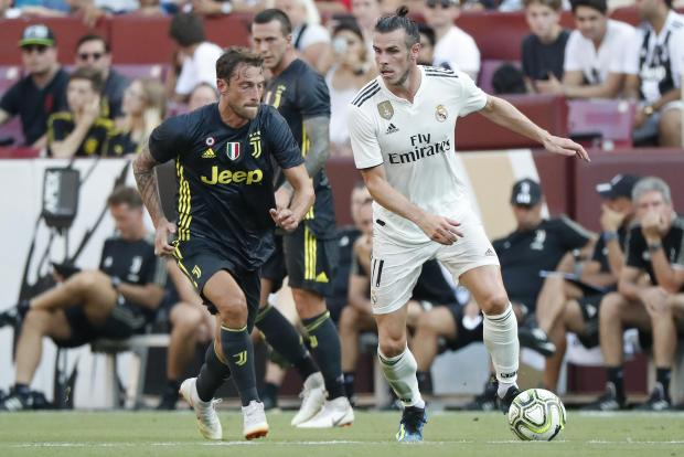 Gareth Bale, of Real Madrid, holds off the challenge of Claudio Marchisio, of Juventus.