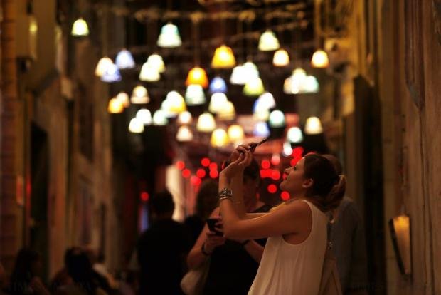 A woman takes photos of street decorations made of glass hanging overhead in Strait Street during Notte Bianca (White Night) celebrations in Valletta on October 3. Photo: Darrin Zammit Lupi