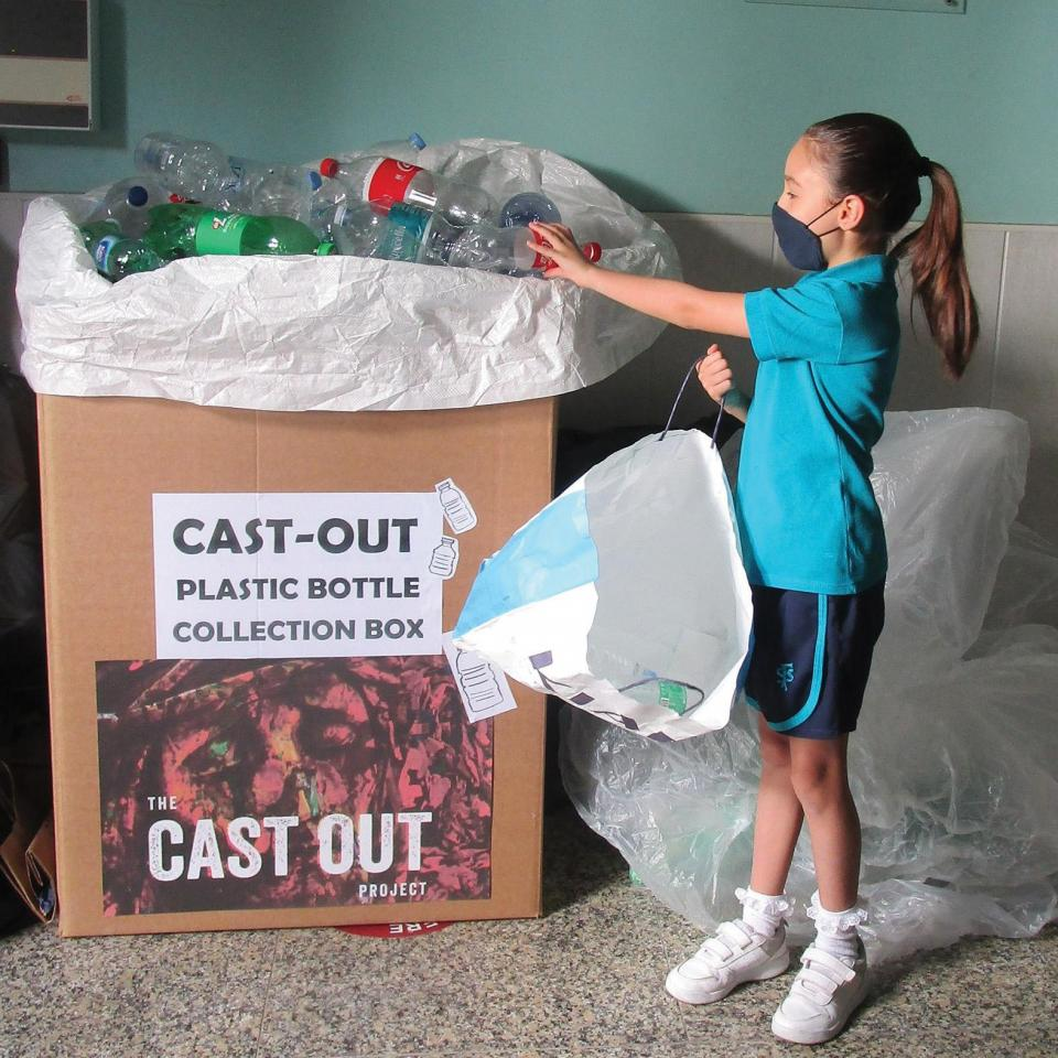A pupil at St Francis school donating recycled bottles.