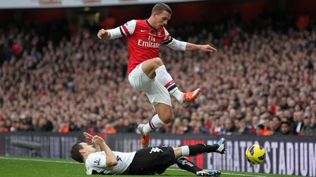 Arsenal's Lukas Podolski (above) battles for the ball with Fulham's Sascha Riether during the Barclays Premier League match at the Emirates Stadium, London. Photo: Sean Dempsey, PA Wire