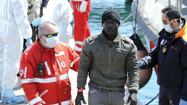 A migrant is helped as he disembarks from a Coast Guard boat in the Sicilian harbour of Palermo on Wednesday.