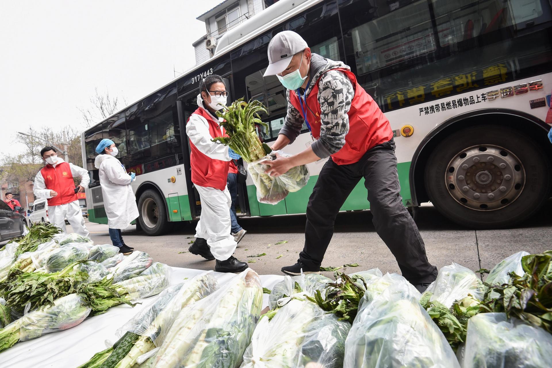 Community volunteers transfer bags of vegetables for residents in Wuhan. Photo: AFP