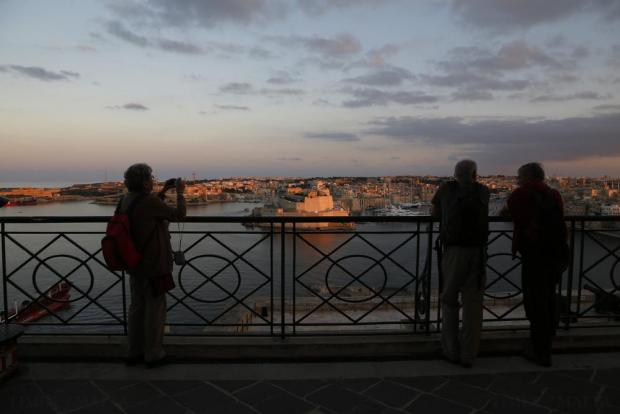 Tourists at the Upper Barrakka Gardens look at Fort St Angelo in Valletta's Grand Harbour at sunset on November 16. Photo: Darrin Zammit Lupi