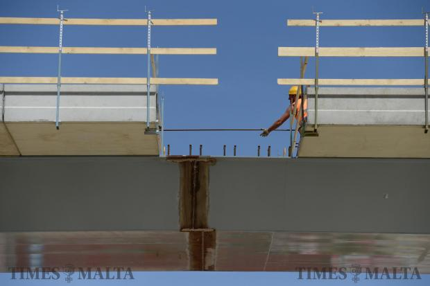 Workers pass a steel rod over a gap in the Kappara flyover on May 5. Photo: Matthew Mirabelli