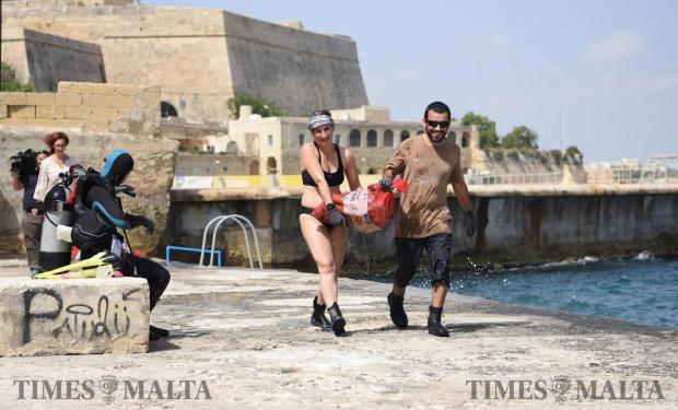 Volunteers carry bottles and other debris found on the seabed during a clean up held in Valletta on June 7. Photo: Mark Zammit Cordina