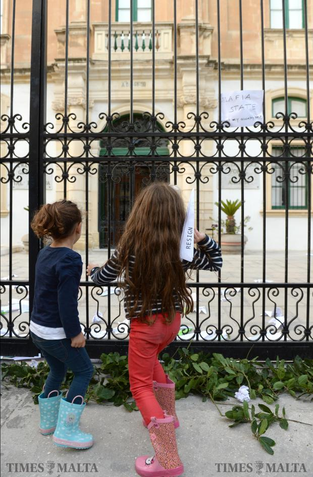 Two young girls attending the sit-in protest in front of the Police HQ in Floriana on November 5, throw a paper plane with a message to the Police Commissioner, who is clinging to his position. Photo: Matthew Mirabelli