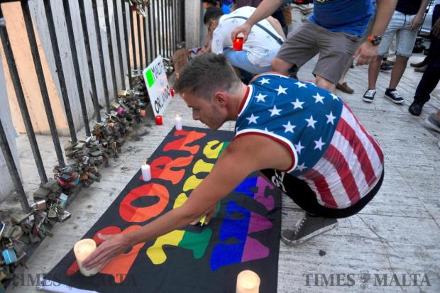 A person lights a candle near the Love monuement in St Julian's on June 17, in a symbolic demonstration of love and peace over hate, triggered by the mass shooting in Orlando, USA leaving 49 people dead. Photo: Steve Zammit Lupi