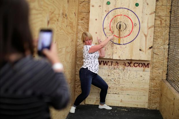 A woman poses with her bullseye hit. Photo: Reuters