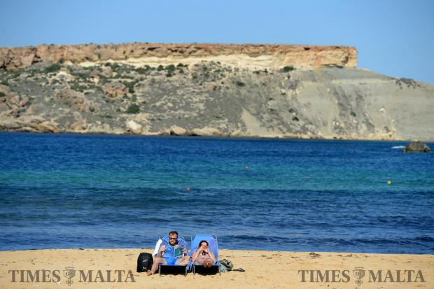A couple enjoy the sun on the beach in Gnejna on a sunny day on October 26. Photo: Matthew Mirabelli