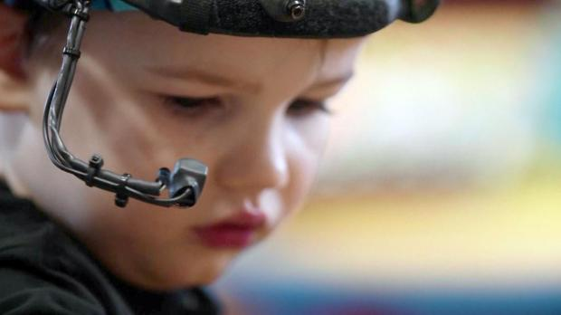 A toddler wears an eye-tracker that measures changes in pupil size. Photo: Reuters