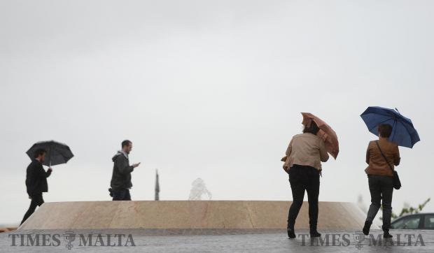 People battle the wind and rain in Valletta on March 21. Photo: Matthew Mirabelli