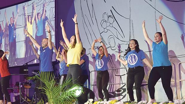 Teachers singing and dancing on stage.