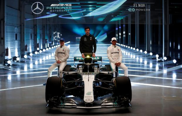 Mercedes' Lewis Hamilton, Valtteri Bottas and Executive Director Toto Wolff pose with the new car during the launch.
