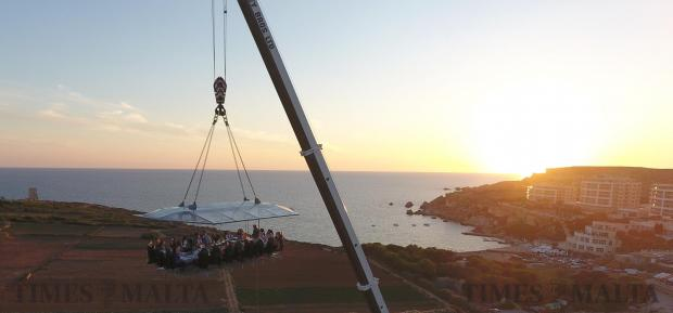 People enjoy dinner whilst suspended around 40 meters from the ground during a dinner in the sky event held in Ghajn Tuffieha on June 21. Photo: Mark Zammit Cordina