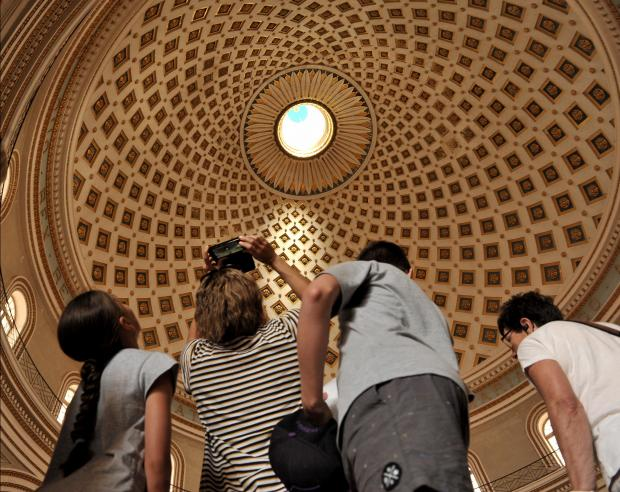 Tourists gaze up in amazement at the interior of the Mosta dome on October 11. Photo: Chris Sant Fournier