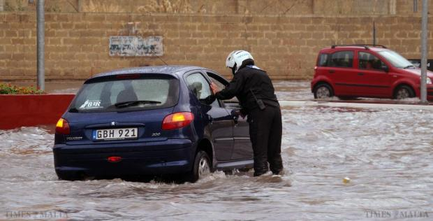 A police officer helps a standed motorist in Msida after heavy rainfall caused flooding on October 2. Photo: Steve Zammit Lupi