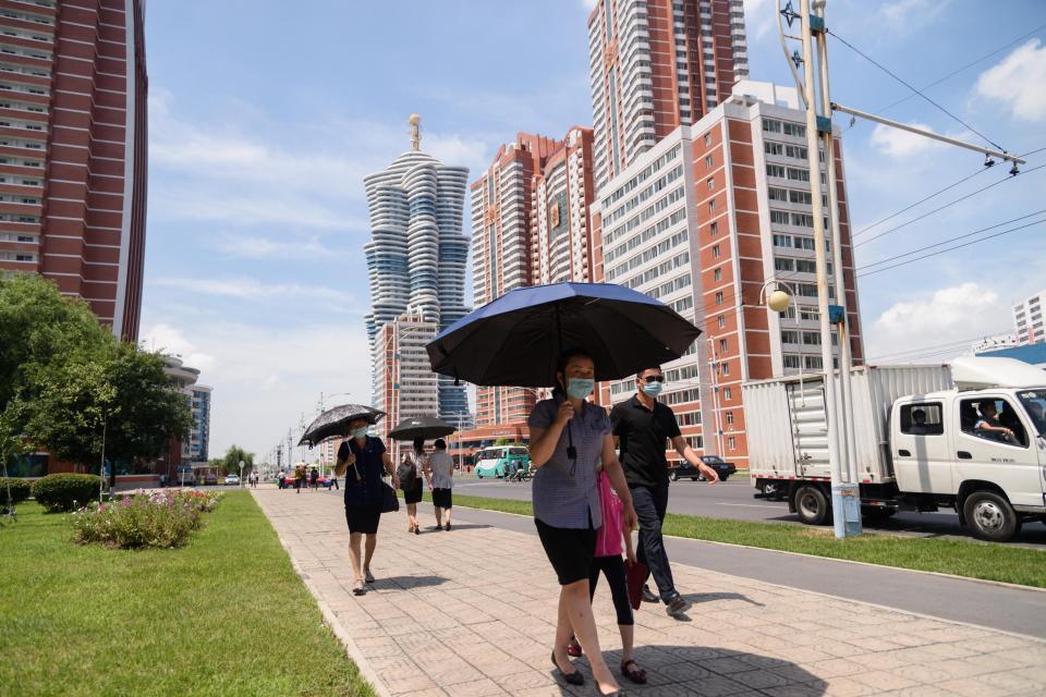 Las personas se refugian bajo paraguas mientras caminan por la calle Mirae durante temperaturas de 34 grados centígrados, en Pyongyang.