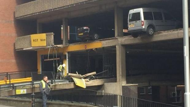 Auto park wall collapse leaves vehicles on building's edge