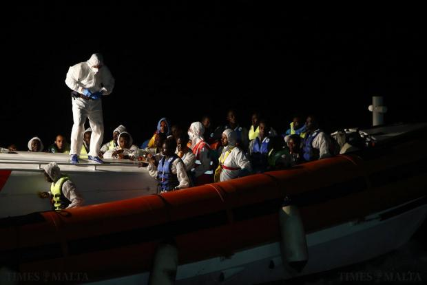 Rescued migrants stand in an Italian Coast Guard vessel after transferring from the Migrant Offshore Aid Station (MOAS) ship MV Phoenix between Libya and the Italian island of Lampedusa on August 3. Some 118 migrants were rescued by the MOAS ship MV Phoenix from a rubber dinghy around 32 kilometres off the coast of Libya on Monday morning. The Phoenix, manned by personnel from international non-governmental organisations Medecins san Frontiere (MSF) and MOAS, is the first privately funded vessel to operate in the Mediterranean. Photo: Darrin Zammit Lupi