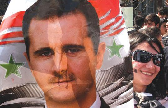 A supporter of Syrian President Bashar al-Assad displaying a poster of him as she demonstrates in Damascus, Syria, on Tuesday. Photo: Bassem Tellawi/PA Wire