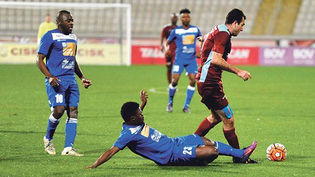 Gżira wing-back Jacob Borg avoids the sliding tackle of Francis Onwudinjo as Mosta team-mate Njongo Priso looks on. Photos: Steve Zammit Lupi