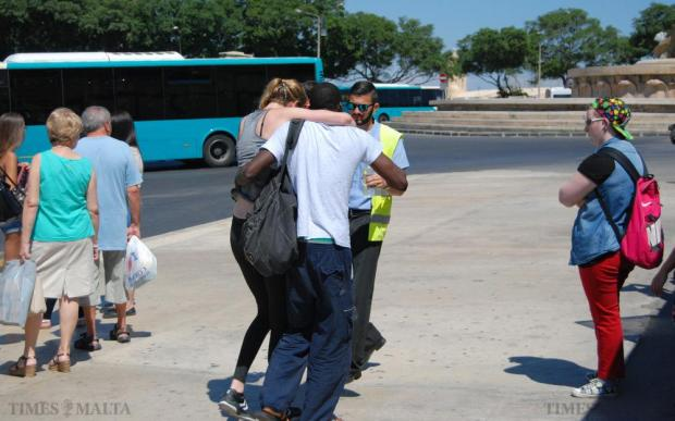 A commuter is helped to an ambulance after she fainted and hit her head against a bench while queuing for the newly introduced Tallinja cards at the Valletta bus terminus on July 1. Photo: Mark Zammit Cordina