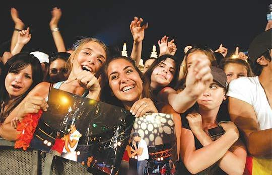 A knight to remember... Sarah Michelle Attard (centre) clutching her photos of last year's dance with Enrique Iglesias, her ticket to the stage once again. Photo: Darrin Zammit Lupi