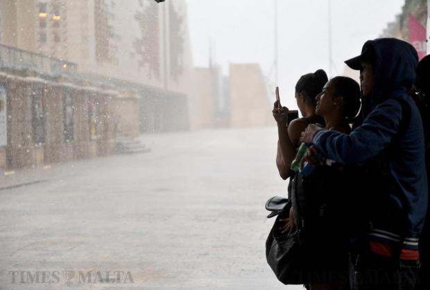 Tourists take shelter under a shop canopy in Republic Street in Valletta during an unseasonal downpour on June 24. Photo: Chris Sant Fournier