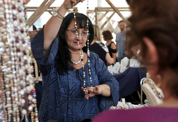 A woman at a stall holds up a necklace for a customer at the Artisanal Fair in Valletta on May 9. Photo: Chris Sant Fournier
