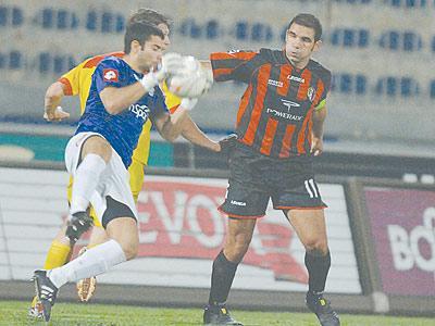 Birkirkara goalkeeper Bernard Paris grabs the ball as Hamrun captain Stefan Sultana looks on.