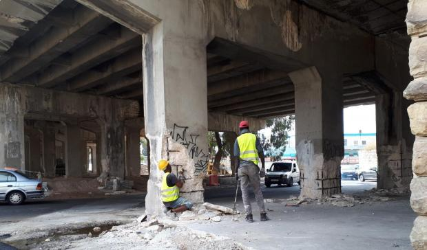 Workers carry out surface works on the flyover bridge.