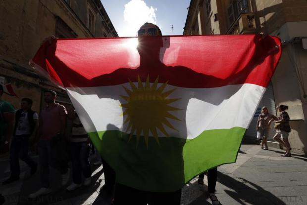 A member of the Kurdish community in Malta carries the Kurdish flag while protesting against Islamic State during a rally in solidarity with the people of the Syrian Kurdish town of Kobani, in Valletta on October 25. Photo: Darrin Zammit Lupi