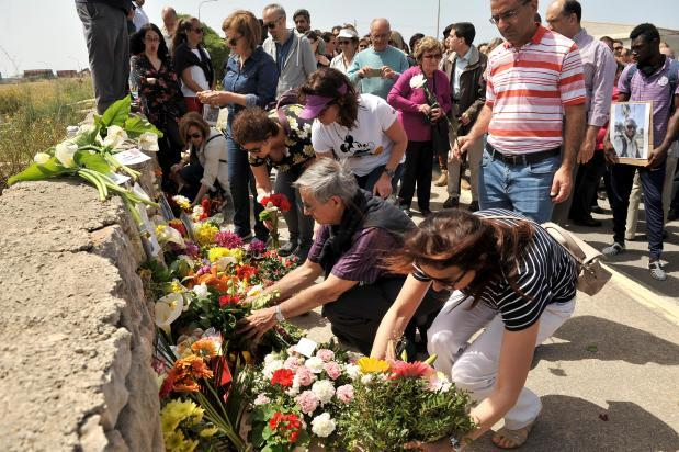 Mourners laying flowers at the site. File photo.