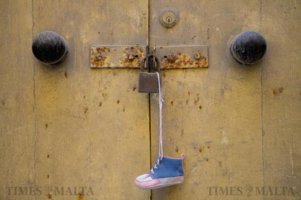 A single baby boot hangs from an old door in Valletta on April 15. Photo: Matthew Mirabelli