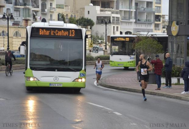 A bus passes alongside competing runners on the final approach to the finish line of the 2015 Mdina 2 Spinola Christmas Road Race in St Julian's on December 20. Photo: Mark Zammit Cordina
