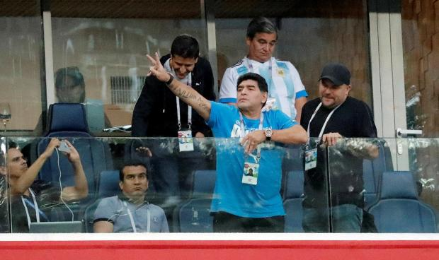 Diego Maradona gestures to the fans from the stands during the match.