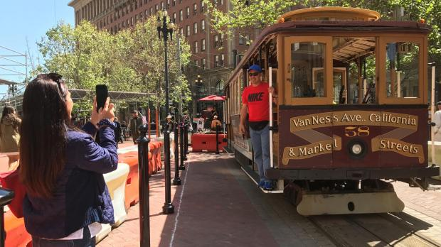 Tourists take pictures of an immobile cable car during a power cut in downtown San Francisco. Photo: Alexandria Sage, Reuters