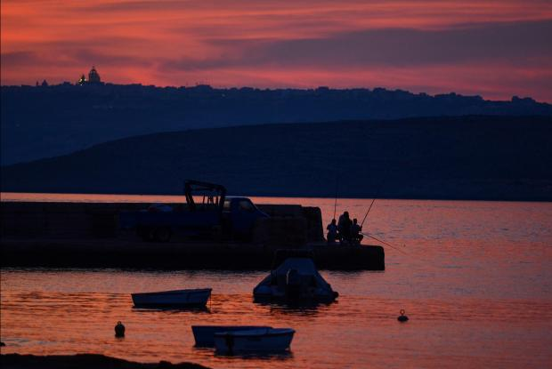 Fishermen enjoy the sunset with Comino and Gozo providing a beautiful backdrop at Marfa Bay on June 21. Photo: Jonathan Borg