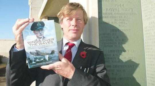 Author Graham Roy Drucker holding a copy of the biography.