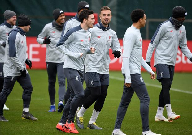 Liverpool's Scottish defender Andrew Robertson (centre) and Liverpool's English midfielder Jordan Henderson takes part in a team training session.