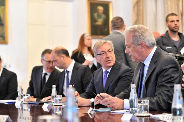 European Commissioner for Migration Dimitris Avramopoulos, right, chats with fellow Commissioner Karmenu Vella prior to a news conference held on April 23, held following a funeral for 24 migrant victims. Italian Home Affairs Minister Angelino Alfano, third from right, is also in picture. Photo: Jason Borg