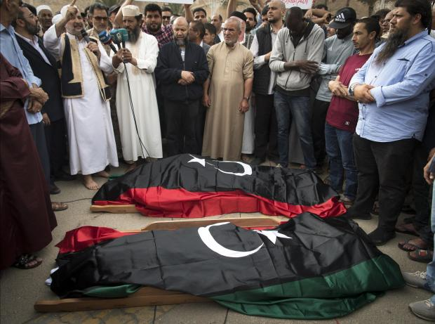 Libyans pray by the bodies of fighters loyal to the Government of National Accord (GNA) during their funeral in the capital Tripoli.